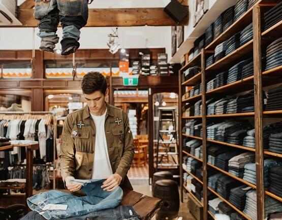 Encompass man folding jeans